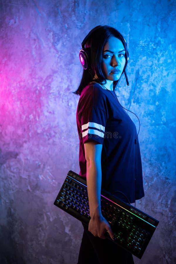 Профессиональный Gamer девушки в видеоигре стратегии MMORPG Она она представляя над красочной голубой и розовой предпосылкой с a стоковое фото