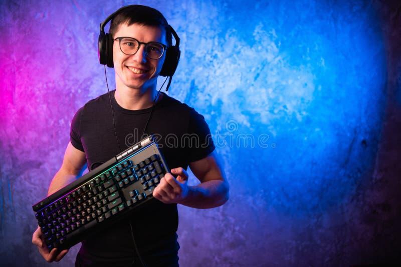 Профессиональный Gamer мальчика держа клавиатуру игры над красочным пинком и голубой неоновой свет стеной Концепция gamers игры стоковое изображение