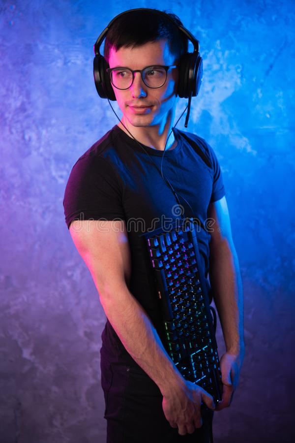 Профессиональный Gamer мальчика держа клавиатуру игры над красочным пинком и голубой неоновой свет стеной Концепция gamers игры стоковое изображение rf