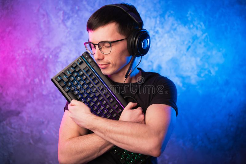Профессиональный Gamer мальчика держа клавиатуру игры над красочным пинком и голубой неоновой свет стеной Концепция gamers игры стоковая фотография