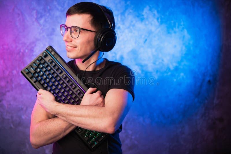 Профессиональный Gamer мальчика держа клавиатуру игры над красочным пинком и голубой неоновой свет стеной Концепция gamers игры стоковое фото rf