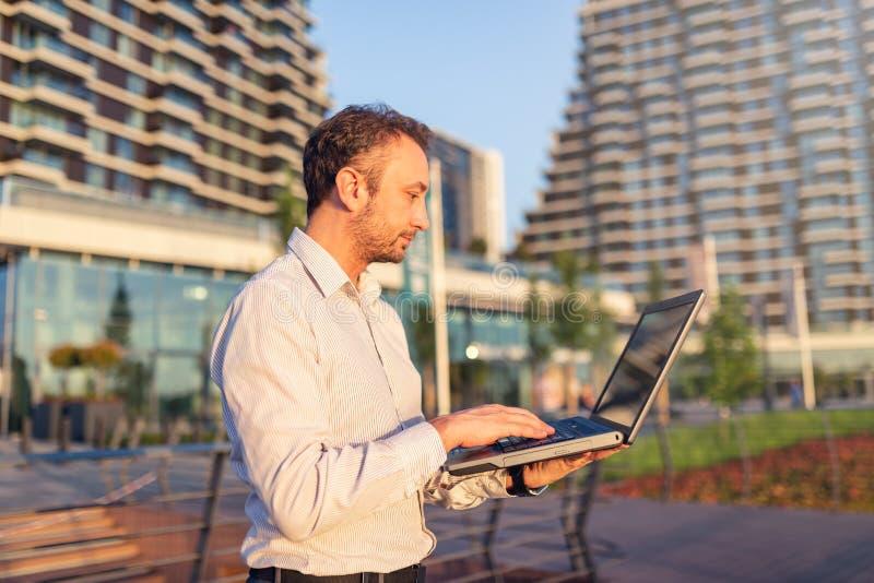 Профессионал дела с ноутбуком вне офиса стоковое фото
