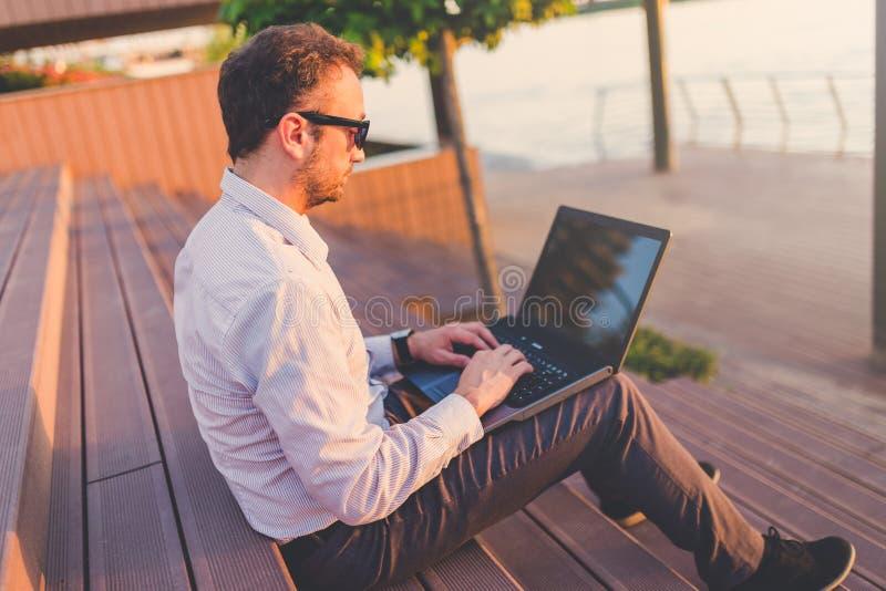 Профессионал дела с ноутбуком сидя на лестнице outdoors стоковые изображения