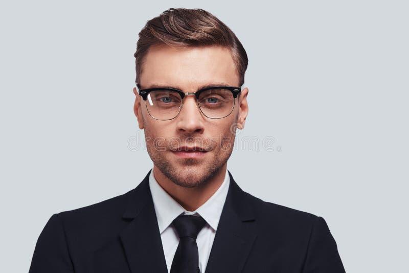профессионал успешный Красивый костюм молодого человека полностью смотря камеру пока стоящ против серой предпосылки стоковое изображение