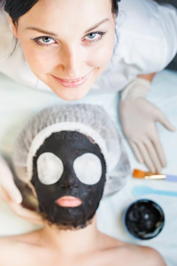 Профессиональная женщина, cosmetologist в салоне курорта прикладывая лицевой щиток гермошлема грязи стоковое изображение