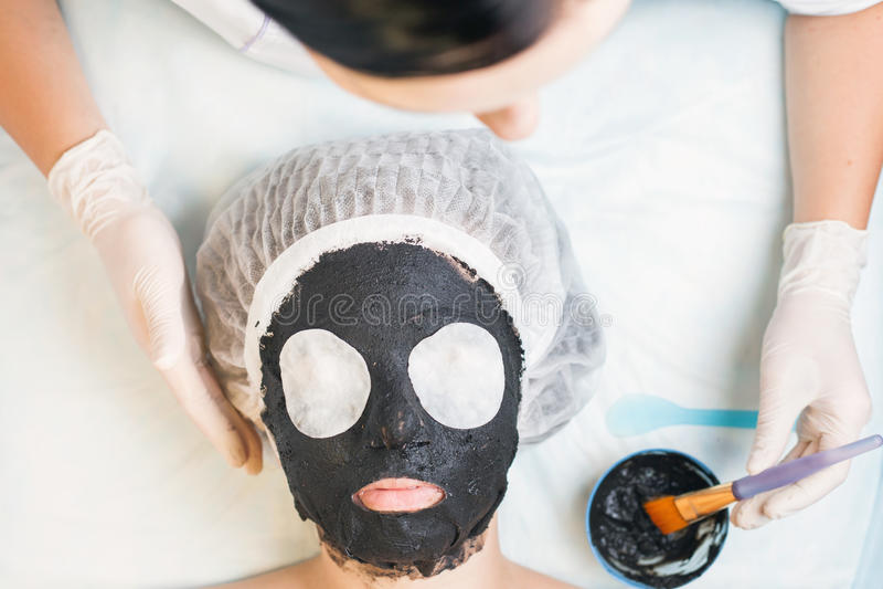 Профессиональная женщина, cosmetologist в салоне курорта прикладывая лицевой щиток гермошлема грязи стоковое фото rf