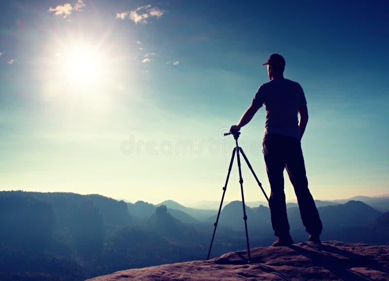 Профессиональное пребывание фотографа с треногой на скале и думать Мечтательный ландшафт fogy, голубой туманный восход солнца в к стоковое фото