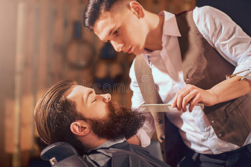 Профессиональные волосы дизайна парикмахера его клиента стоковое изображение rf
