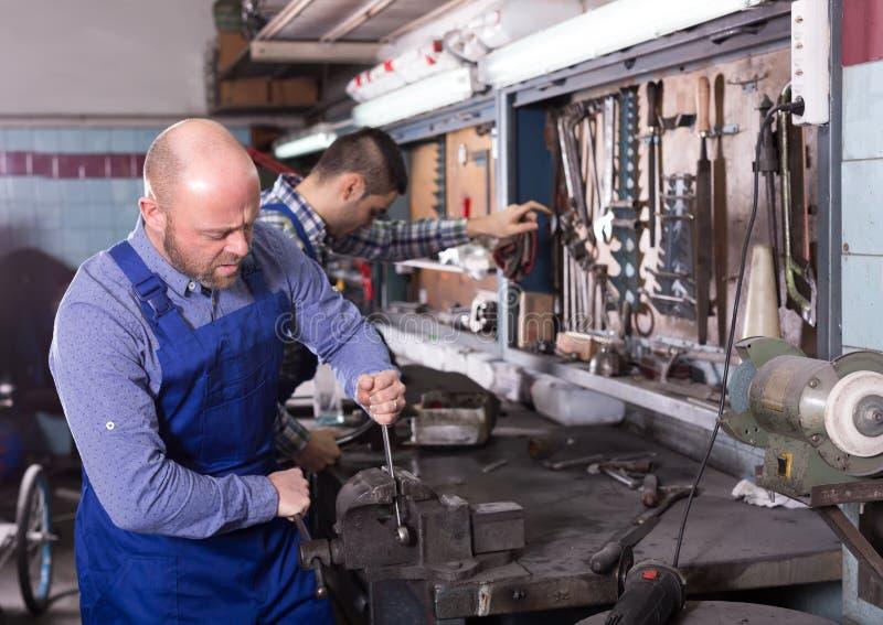 Профессиональные механики в ремонтной мастерской стоковые фото