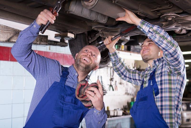 Профессиональные механики ремонтируя автомобиль стоковые изображения