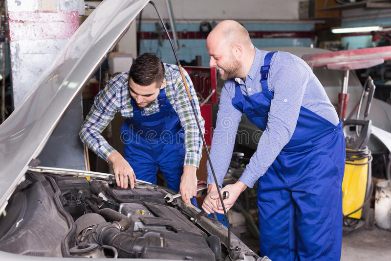 Профессиональные механики ремонтируя автомобиль стоковое изображение rf