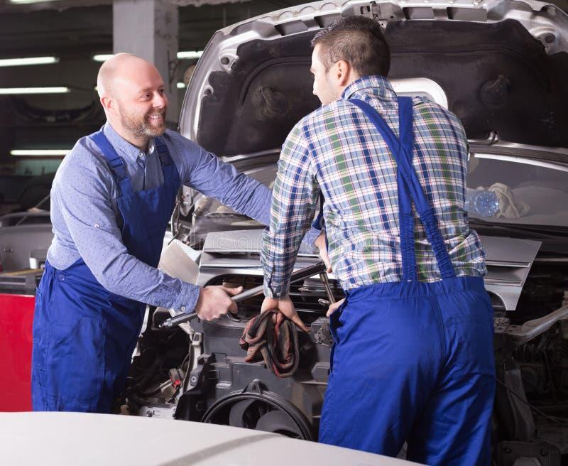 Профессиональные механики ремонтируя автомобиль стоковые изображения rf