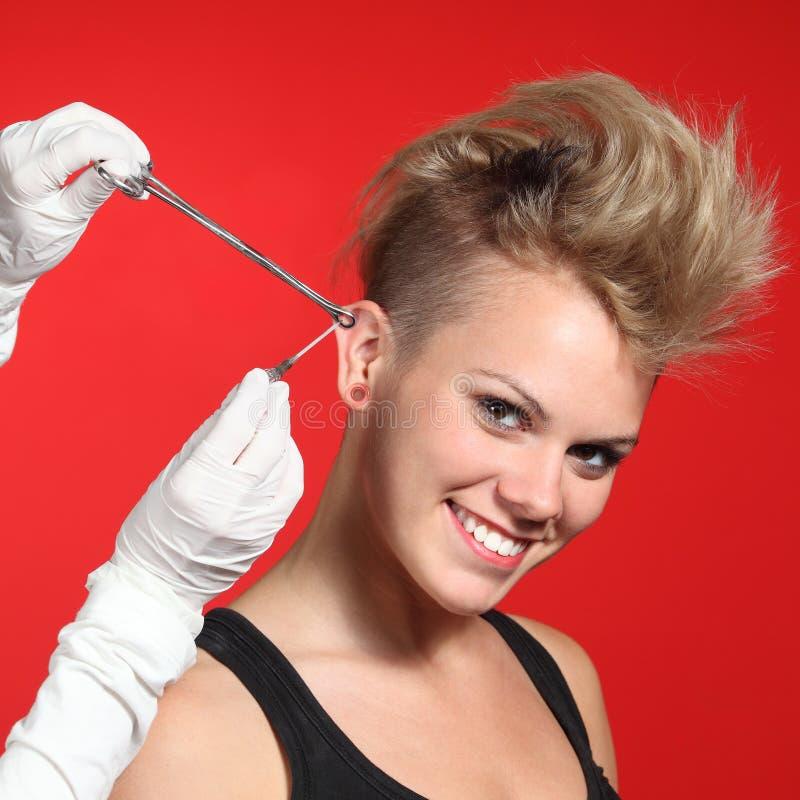 Профессиональные руки делая piercing отверстие к женщине моды стоковые фотографии rf