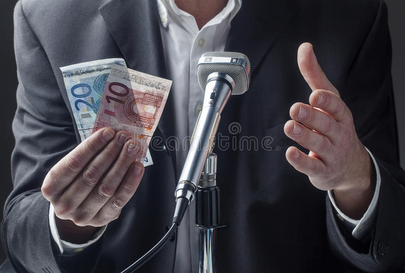 Профессиональный говорить к micro с деньгами в руках стоковое изображение rf