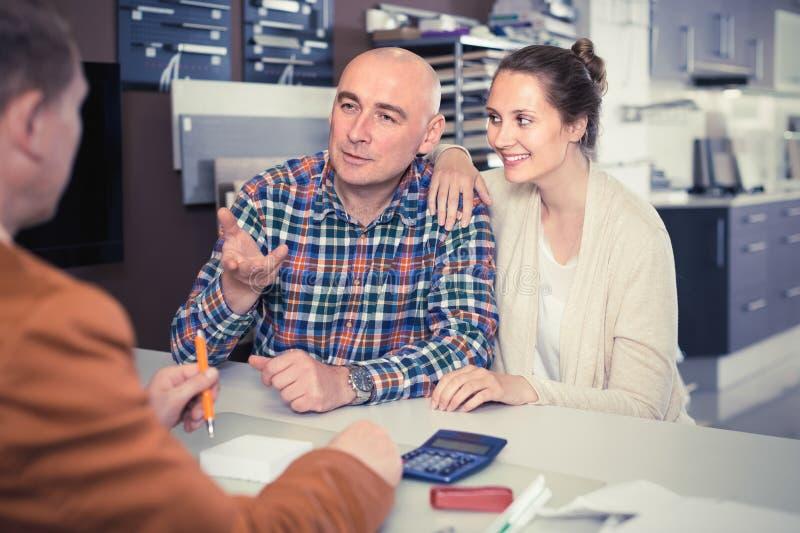 Профессиональный мужской продавец работая с клиентом в магазине стоковые изображения