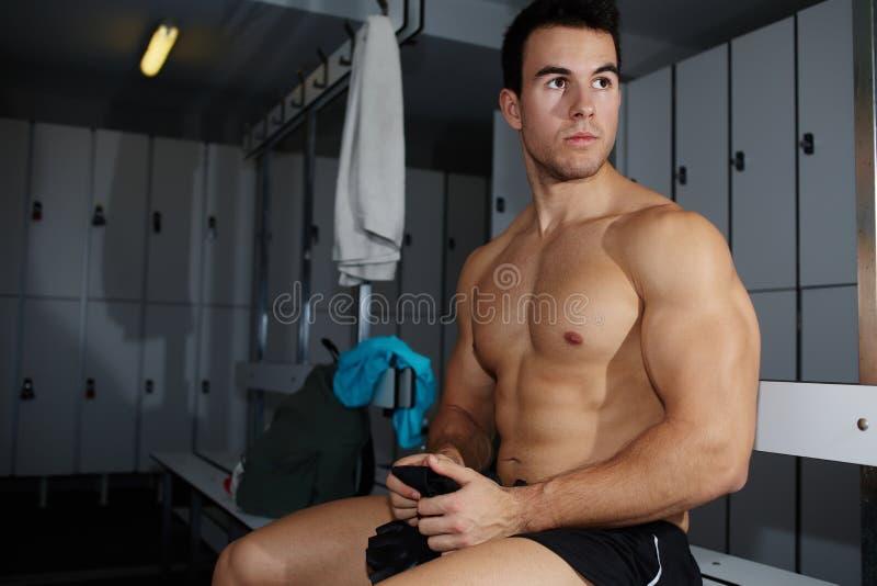 Профессиональный спортсмен извлекая перчатки поднятия тяжестей сидя в раздевалке спортзала стоковое изображение rf
