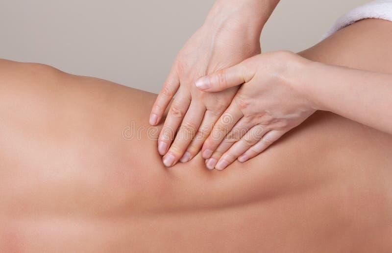 Профессиональный терапевт работая на более низкой задней мышце стоковое изображение