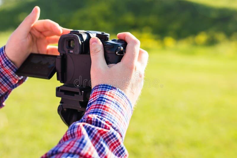 Профессиональный фотограф регулирует камеру перед снимать, руки стоковые изображения