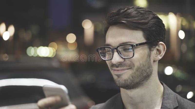 3/4 профилей усмехаясь человека отправляя СМС на улице стоковая фотография rf