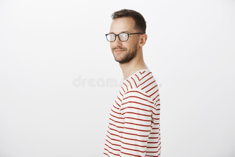 Профилируйте портрет дружелюбного уверенно яркого парня в striped пуловере, поворачивая на камеру и усмехаясь обширно, чувствующ стоковая фотография rf