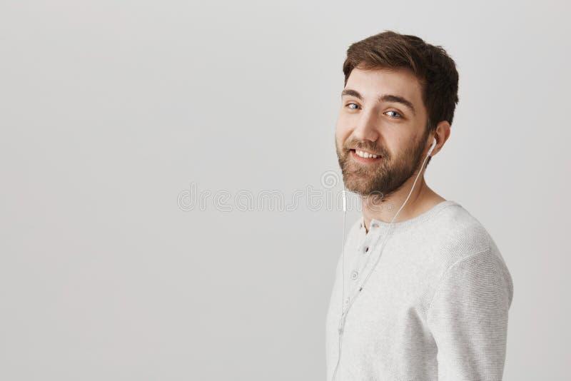 Профилируйте портрет интересного симпатичного бородатого человека смотря и усмехаясь на камере пока носящ наушники, говоря стоковая фотография
