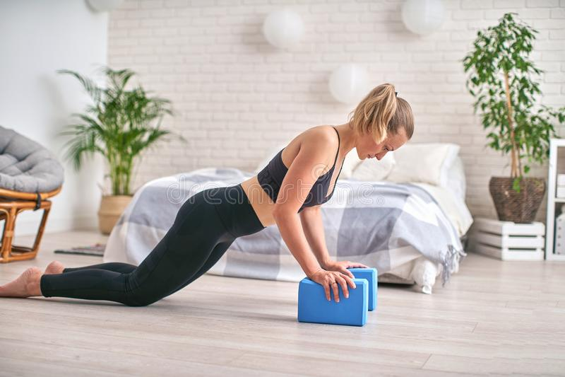 Профиль взгляда со стороны хорошо сформированного спортсмена Она остается в планке и используется блоки йоги для запястьев стоковое изображение