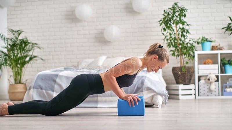 Профиль взгляда со стороны хорошо сформированного спортсмена Она остается в планке и используется блоки йоги для запястьев стоковые изображения
