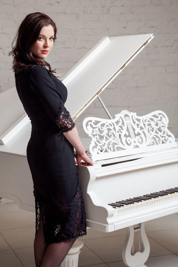 Профиль взгляда со стороны чувственной женщины брюнета в положении платья шнурка черном классическом около белого рояля и смотрет стоковое фото rf