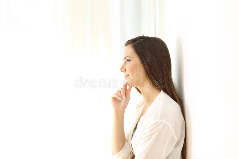 Профиль женщины думая дома на белизне стоковые фото