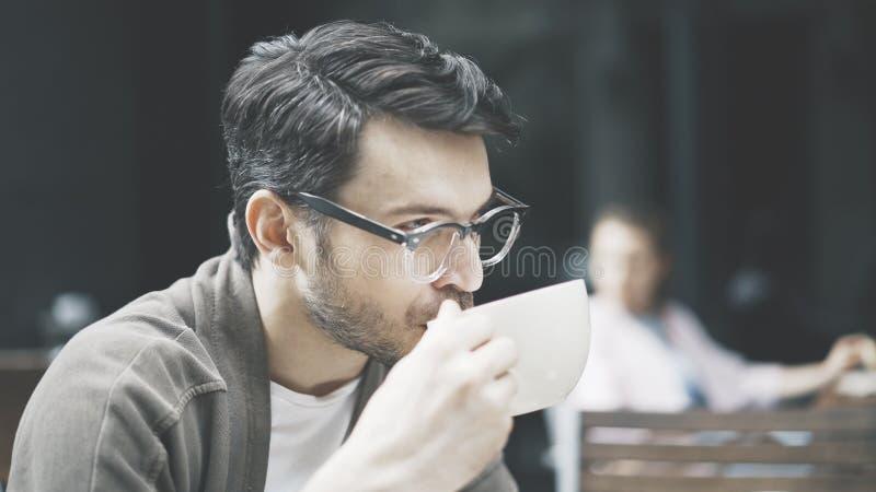 Профиль красивого человека в eyeglasses выпивая кофе стоковые изображения rf