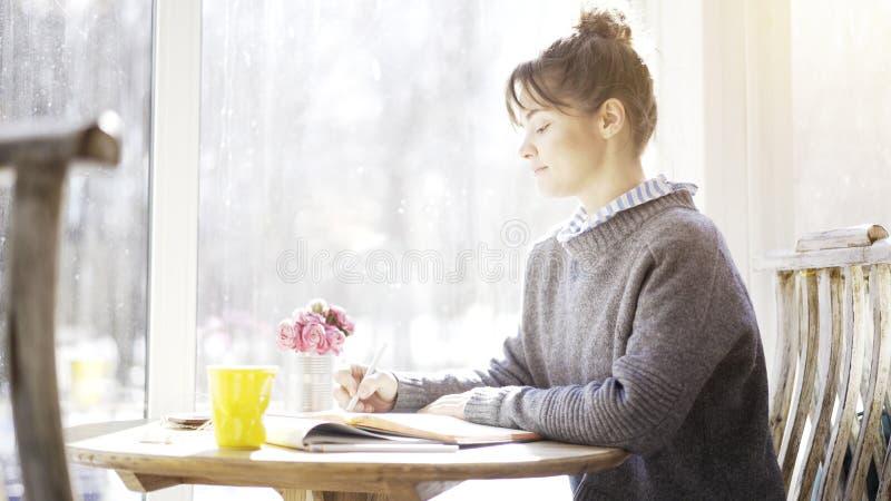 Профиль молодой девушки брюнет читает смотреть в тетрадь в кафе стоковые изображения rf