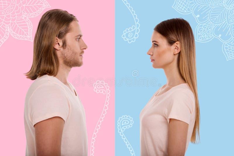 Профиль молодых пар стоя перед одином другого стоковое изображение