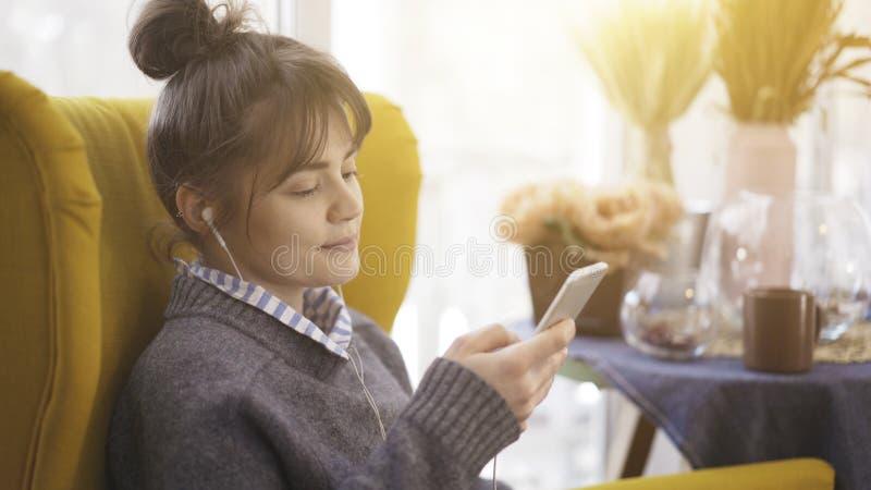 Профиль портрета девушки в наушниках держа телефон стоковые изображения rf