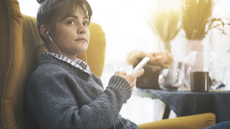 Профиль портрета усмехаясь девушки в наушниках держа телефон стоковая фотография rf