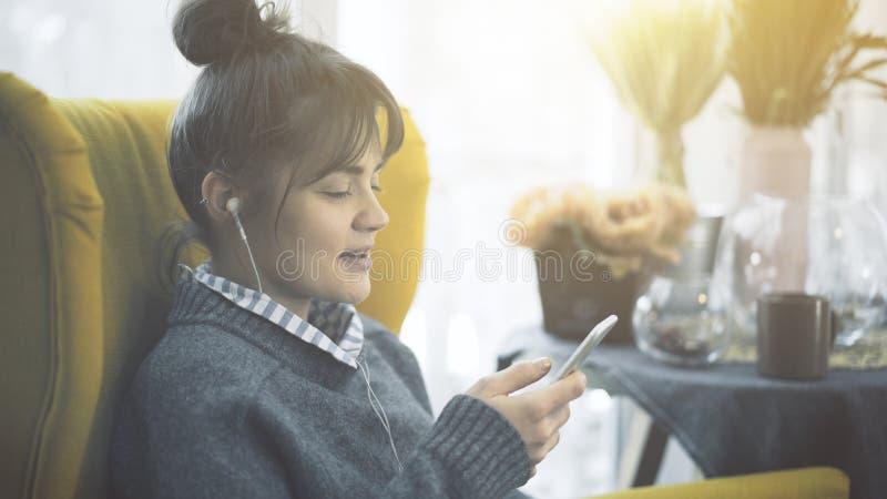 Профиль портрета усмехаясь девушки в наушниках держа телефон стоковое изображение