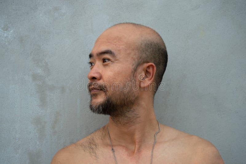 Профиль портрета человека бороды 30-40s лысого японского топлесс крутого на серой предпосылке бетонной стены стоковые изображения rf