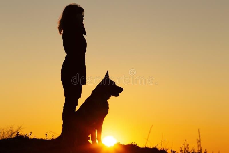 Профиль силуэта молодой женщины и собаки немецкой овчарки смотря в расстоянии на заходе солнца, любимца сидя около ноги девушки н стоковые фото