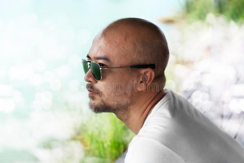 Профиль солнечных очков случайной взрослой лысой бороды 40s нося в белой футболке со светлым bokeh предпосылки воды естественной стоковые фото