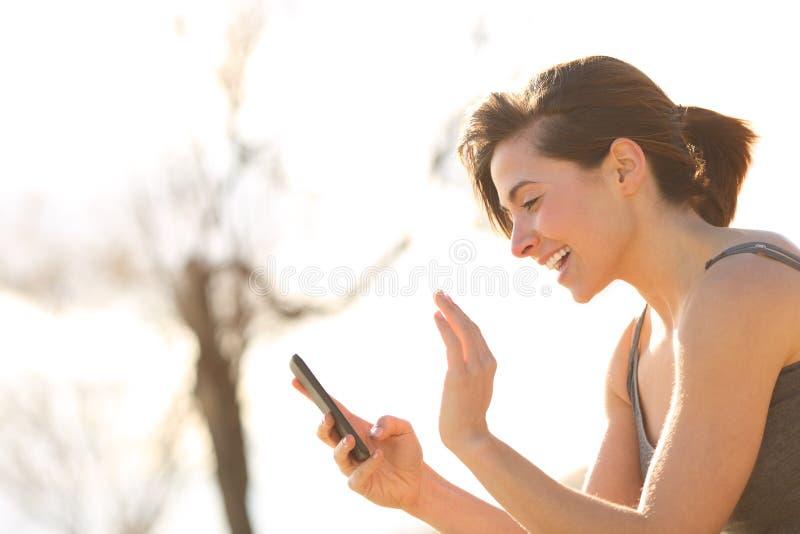 Профиль счастливой женщины имея видео- звонок стоковая фотография