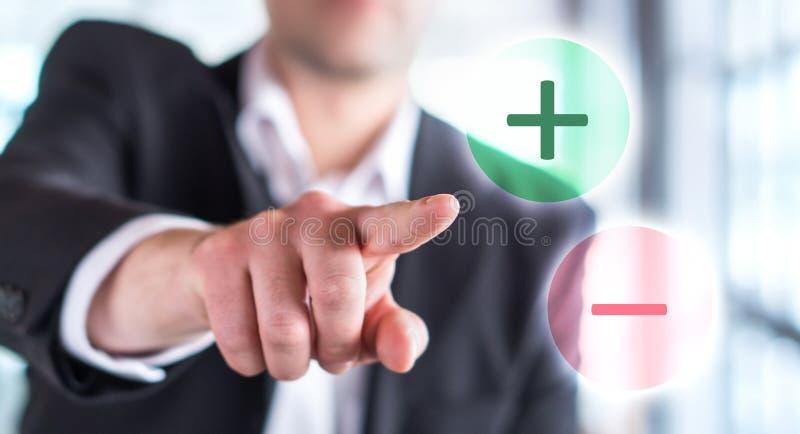 Профи - и - концепция жуликов Бизнесмен касаясь плюс или минус стоковые изображения