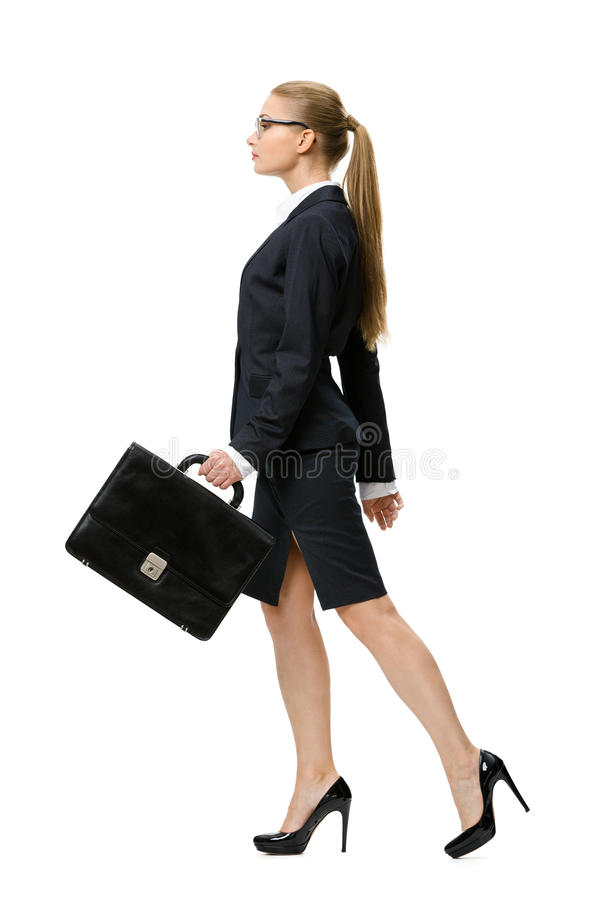 Профиль идя бизнес-леди с чемоданом стоковые фото