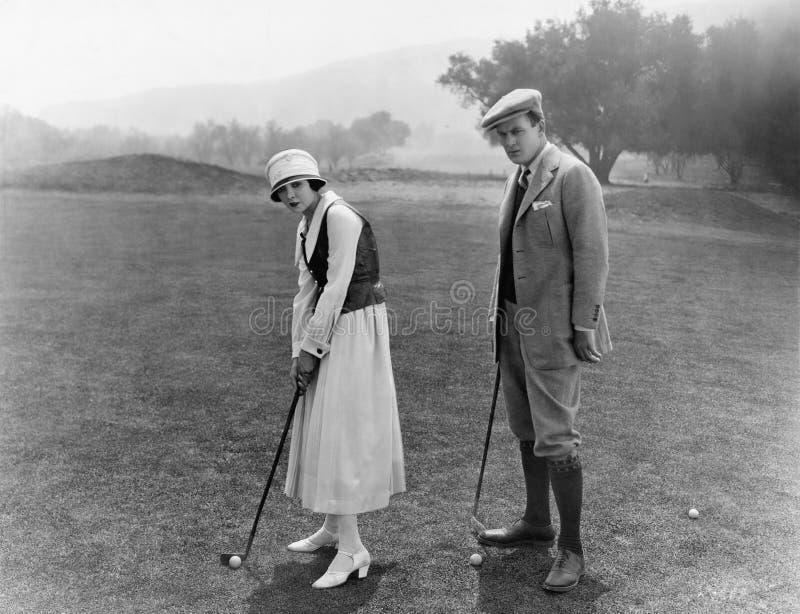 Профиль пары играя гольф в поле для гольфа (все показанные люди более длинные живущие и никакое имущество не существует Warr пост стоковое фото
