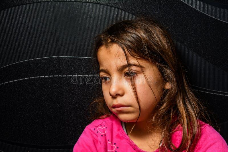 Профиль унылой маленькой девочки сидит в угле комнаты стоковое изображение
