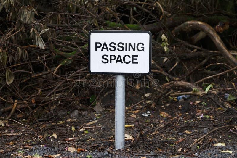 Проходить знак космоса в предпосылке полесья темной на дорогу стоковые изображения