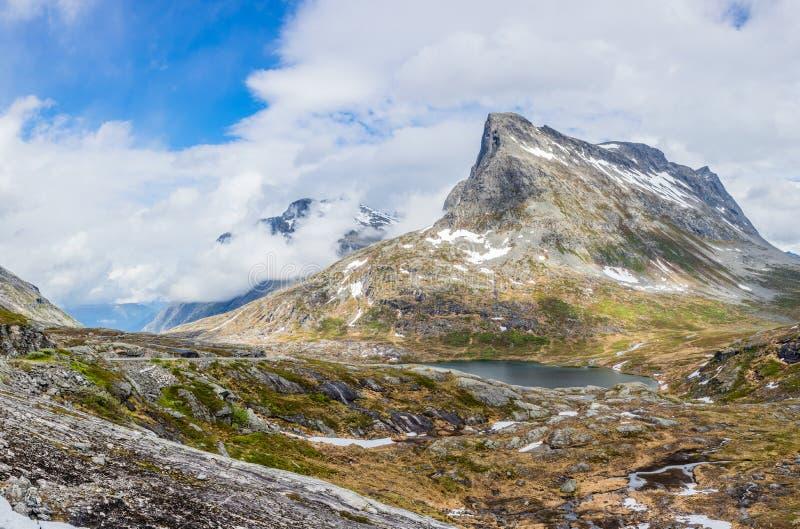 Проход в горах со снежными пиками вокруг панорамы озера Alnesvatnet, путем trolles, Trollstigen, муниципалитетом Rauma, больше стоковое изображение