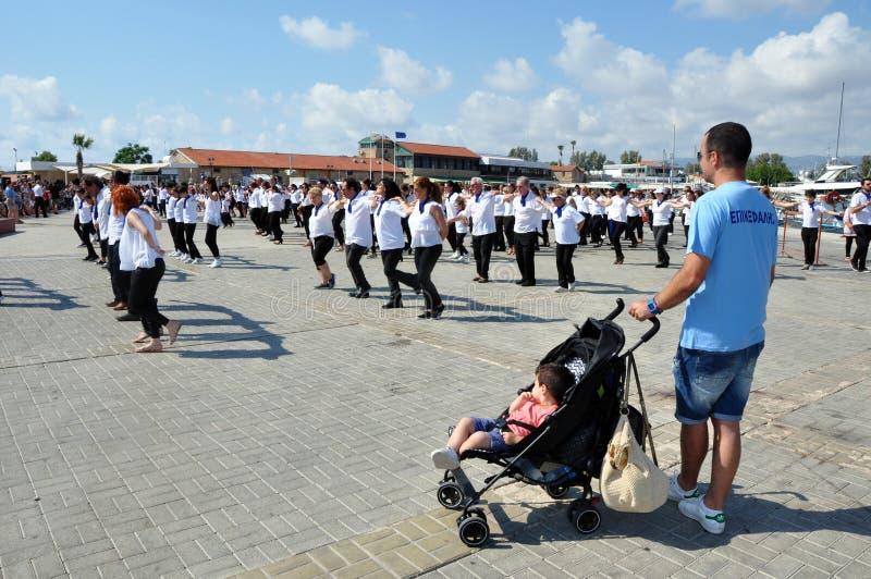 Прохожий наблюдает flashmob Paphos танца hasapiko стоковые изображения rf
