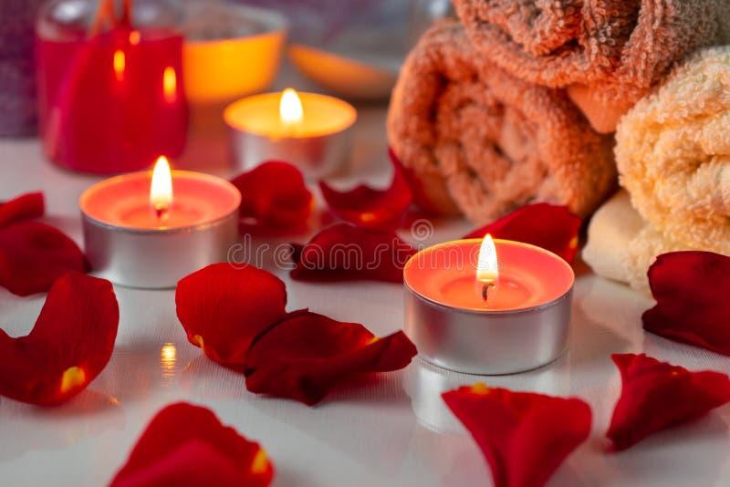 Процедуры спа установили с надушенными маслом, свечами, лепестками розы и цветками стоковая фотография rf