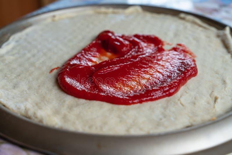 процесс варить пиццу тонкий мазок теста пиццы с кетчуп стоковое фото