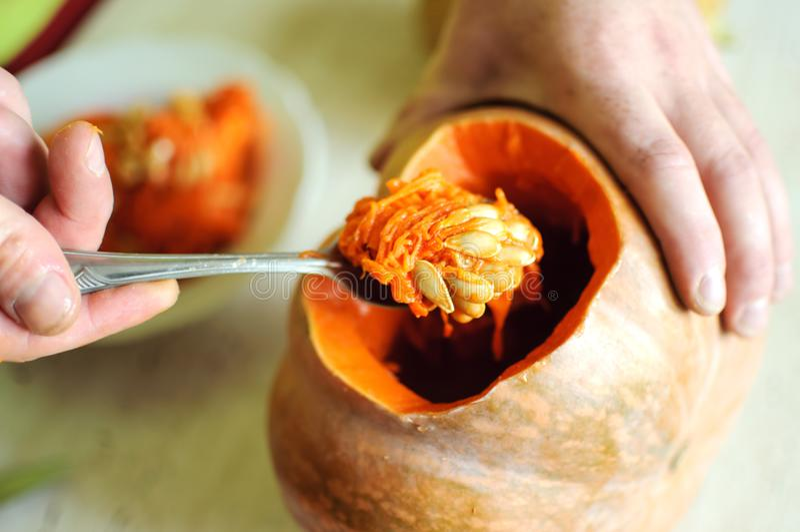 Процесс вырезывания тыквы хеллоуина, мужские руки с ложкой, семена и остатки на кухонном столе стоковая фотография rf