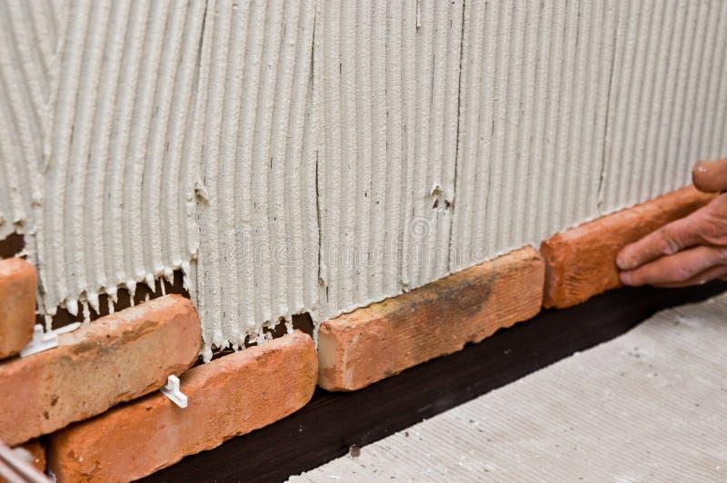 Процесс делать красную кирпичную стену, домашнюю реновацию стоковое изображение